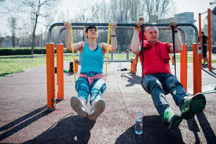 Calisthenics class at outdoor gym, mature man and young woman exercising on parallel barsの写真素材 [FYI03807619]