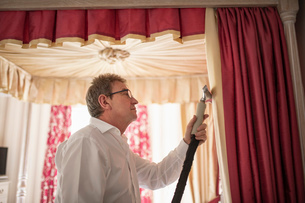 Curtain fitter using steam on material of four poster bedの写真素材 [FYI03807722]