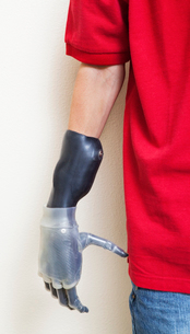 Cropped image of man with prosthetic hand over gray backgrouの写真素材 [FYI03807830]