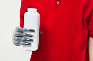 Mid section of a man holding bottle with prosthetic hand oveの写真素材 [FYI03807831]
