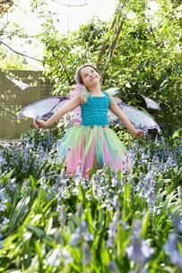 Young girl (5-6) in flower garden wearing fairy costumeの写真素材 [FYI03807845]