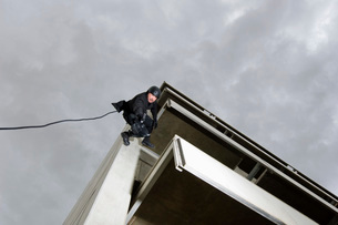 SWAT Team Officer Rappelling and Aiming Gunの写真素材 [FYI03807856]