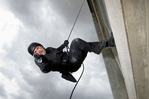 SWAT Team Officer Rappelling from Buildingの写真素材 [FYI03807857]