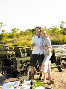Couple on picnic during safari smiling jeep in backgroundの写真素材 [FYI03807867]