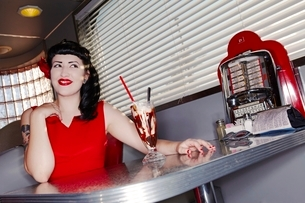 Retro woman in red dress in American dinerの写真素材 [FYI03807892]
