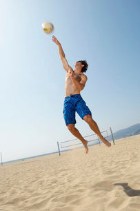 Young man jumping hitting volleyball on beachの写真素材 [FYI03807906]