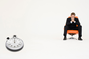 Anxious businessman sitting on chair with stopwatch showingの写真素材 [FYI03807956]
