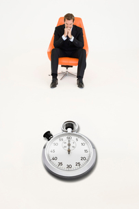 Anxious businessman sitting on chair with stopwatch in frontの写真素材 [FYI03807957]