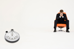 Worried businessman sitting on chair with stopwatch represenの写真素材 [FYI03807958]