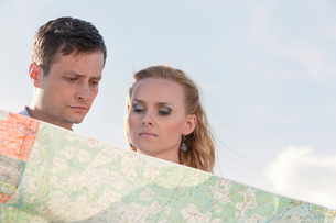 Couple reading map against skyの写真素材 [FYI03808053]