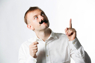 Portrait of an attractive young man wearing a retro style fake mustache.の写真素材 [FYI03808067]