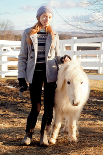 Young woman standing with miniature ponyの写真素材 [FYI03808345]