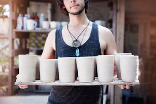 Young potter holding ceramic works, mid sectionの写真素材 [FYI03808403]