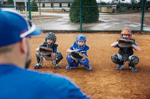 Rear view of coach training baseball catchers on fieldの写真素材 [FYI03808808]