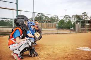 Side view of baseball catchers crouching on fieldの写真素材 [FYI03808813]
