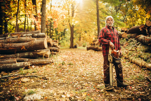 Portrait of confident lumberjack holding chainsaw in forestの写真素材 [FYI03808844]