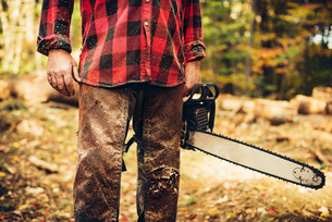 Midsection of lumberjack holding chainsaw in forestの写真素材 [FYI03808848]