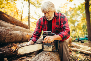 Male lumberjack examining chainsaw while sitting on log in forestの写真素材 [FYI03808849]