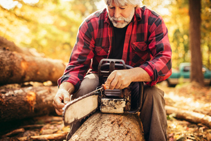 Mature male lumberjack examining chainsaw while sitting on log in forestの写真素材 [FYI03808853]