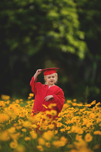 Smiling girl wearing graduation gown standing amidst yellow flowers on fieldの写真素材 [FYI03809163]