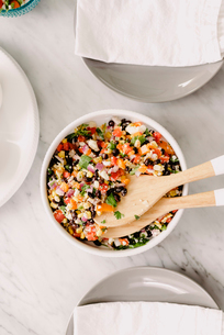 Overhead view of salad in bowl with wooden spoons on tableの写真素材 [FYI03809593]