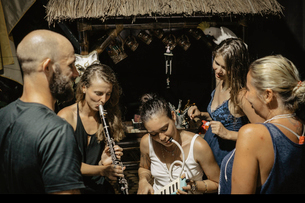 Friends looking at women playing wind instruments in tourist resortの写真素材 [FYI03810436]