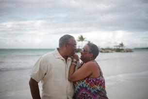 Happy senior couple at beach against cloudy skyの写真素材 [FYI03810525]