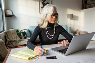 Serious senior woman using laptop computer while paying bills at homeの写真素材 [FYI03810559]