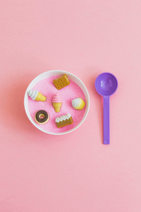 Overhead view of various sweet food toys in bowl with spoon on pink backgroundの写真素材 [FYI03810596]