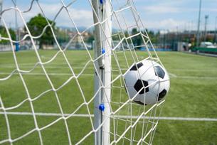 Soccer ball hitting net against skyの写真素材 [FYI03810671]