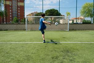 Rear view of boy kicking soccer ball towards net on fieldの写真素材 [FYI03810676]