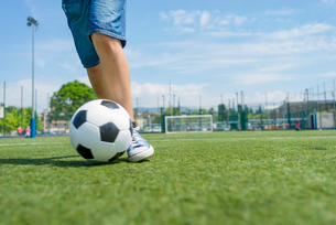 Low section of boy practicing soccer on field against skyの写真素材 [FYI03810678]