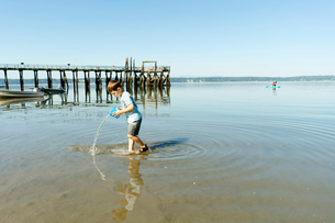 Side view of boy playing with water while standing in sea against clear blue sky during sunny dayの写真素材 [FYI03810768]