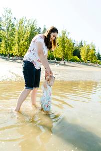 Side view of mother with cute daughter standing in sea against clear skyの写真素材 [FYI03810774]