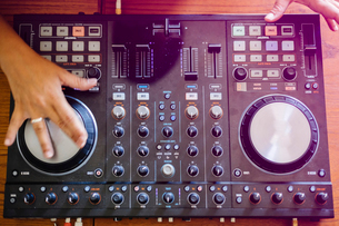 Cropped hands of female DJ mixing sound on table in recording studioの写真素材 [FYI03810785]