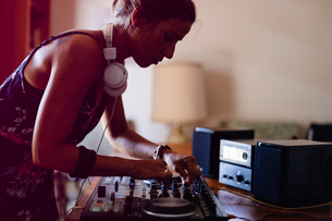 Side view of female DJ mixing sound while standing in recording studioの写真素材 [FYI03810786]