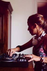 Side view of female DJ mixing sound while sitting in recording studioの写真素材 [FYI03810788]