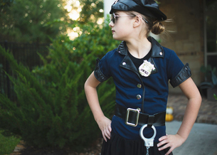 Confident girl wearing police costume with hands on hip standing against plants in yard during Halloの写真素材 [FYI03810832]