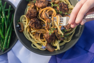 fork lifing spaghetti, with spicy meatballs with green beansの写真素材 [FYI03810879]