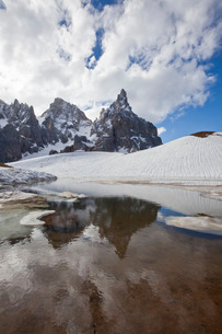 Thawing snow leaving some puddles at the foot of the Pale di San Martino by San Martino di Castrozzaの写真素材 [FYI03811608]