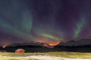 Northern Lights illuminates the wooden cabin at Svensby, Lyngen Alps, Troms, Lapland, Norway, Scandiの写真素材 [FYI03811894]