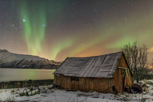 The Northern Lights illuminates the wooden cabin, Svensby, Lyngen Alps, Troms, Lapland, Norway, Scanの写真素材 [FYI03811895]