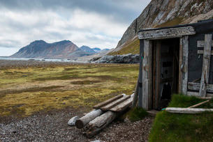 Abandoned hut on Alkhornet with a huge rock in the background, Svalbard, Arcticの写真素材 [FYI03812187]