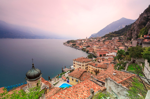 Pink sunrise lights up Lake Garda and the typical town of Limone Sul Garda, province of Brescia, Itaの写真素材 [FYI03812328]