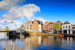 Blue sky and clouds on typical houses reflected in the canal of the River Spaarne, Haarlem, North Hoの写真素材 [FYI03812382]