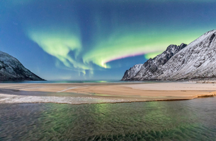 Green lights of Northern Lights (aurora borealis) reflected in the cold sea surrounded by snowy peakの写真素材 [FYI03812390]