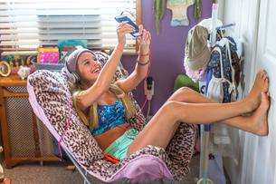 Teenager with earphones taking selfie on lazy chair in bedroomの写真素材 [FYI03813187]