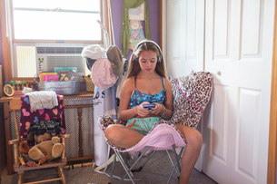 Teenager using smartphone on lazy chair in bedroomの写真素材 [FYI03813188]