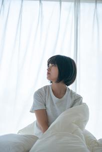 ベッドで起き上がる若い女性の写真素材 [FYI03813691]