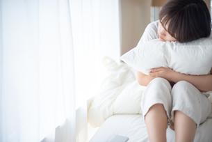 枕を抱える若い女性の写真素材 [FYI03813702]